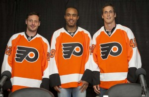 From left, recently acquired Mark Streit, Ray Emery, and Vincent Lecavalier don their new Philadelphia Flyers sweaters during a news conference in the Hall of Fame room at the Wells Fargo Center in Philadelphia July 9.