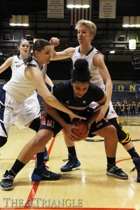 Freshman Sarah Curran (left) and redshirt sophomore Jackie Schluth (right) pressure Amencie Mercer of Northeastern University during Drexel's 55-52 win Jan. 26.