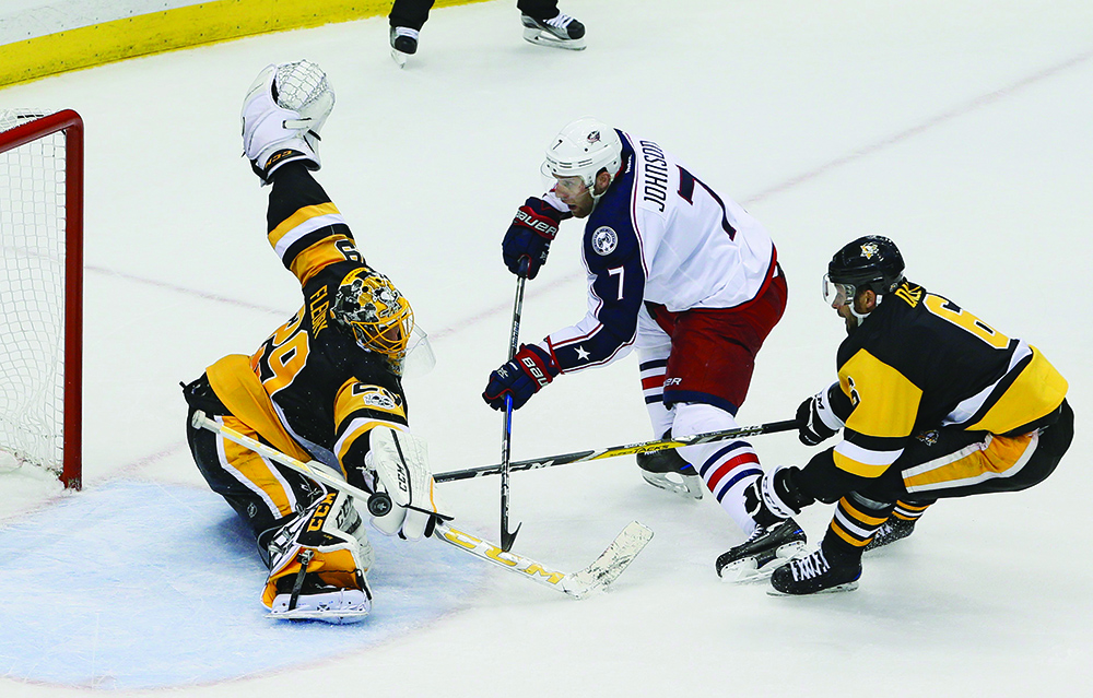 Pittsburgh Penguins goalie Marc-Andre Fleury (29) stops a shot from the Columbus Blue Jackets' Jack Johnson, middle, who gets behind the Penguins' Matt Cullen during the second period of Game 5 in the Eastern Conference quarterfinals at PPG Paints Arena in Pittsburgh on Thursday, April 20, 2017. The Penguins won, 5-2, to win the series 4-1. (Adam Cairns/Columbus Dispatch/TNS)
